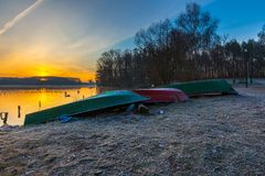 Lake shore with fisherman's boats in colorful landscape Stock Images