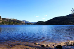Lake, shore and mountain. Blue lake, and mountain forward, with a clean water Royalty Free Stock Photo