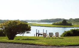 Lake Shore. Peaceful shore of the lake with lawn, shrubs and beach chairs Stock Photo