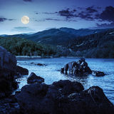 Lake shore with stones near forest on mountain at night Royalty Free Stock Images