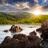 Lake shore with stones near forest on mountain at sunset Stock Image