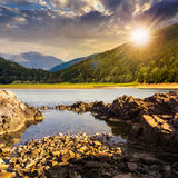 Lake shore with stones near pine forest on mountain at sunset Royalty Free Stock Image