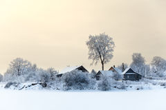 Lake shore with timber houses at winter season with sunset sky Stock Photography