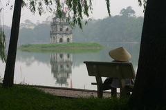 Lake side. Lady relaxing on the banks of Hoan Kiem Lake, Hanoi Stock Photo
