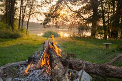 Lake side campfire with wood burning stock images