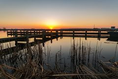 Bright and colorful sunset over a lake with a pier along the lake `Rottemeren` in The Netherlands royalty free stock photography