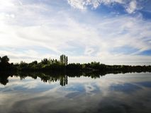 Lake with sky and clouds reflecting in tranquil River. Lake with blue sky and clouds reflecting in tranquil River Royalty Free Stock Images