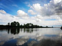 Lake with sky and clouds reflecting in tranquil River. Lake with blue sky and clouds reflecting in tranquil River Royalty Free Stock Image