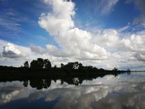Lake with sky and clouds reflecting in tranquil River. Lake with blue sky and clouds reflecting in tranquil River Stock Photo