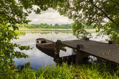 Lake with small boat Stock Images
