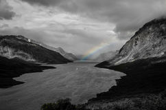 Lake with a small boat and a rainbow. Photo in black and white Stock Photography