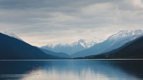 Lake and snow capped mountains Stock Photos