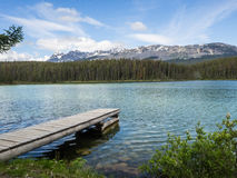 Lake and snow capped mountains with dock Stock Photos