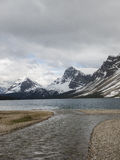 Lake and snow capped mountains on stormy day Stock Photography