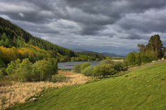 A lake in snowdonia under a grey cloudy sky. Lake in snowdonia under a grey cloudy sky Stock Image