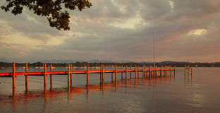 Lake Starnberg. Reflections and jetty at Lake Starnberg  in the evening light Stock Image