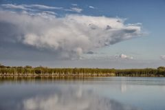 Lake in the steppe. Summer landscape in the steppe with a lake and clouds royalty free stock image