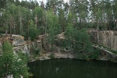 A lake in a stone quarry surrounded by trees. Korostyshevsky canyon. Zhytomyr region. . Royalty Free Stock Image