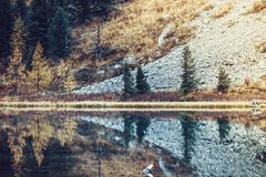 Lake with stones and trees on the shore. Travelling in the mountains in autumn weather royalty free stock photo