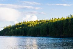 Lake summer view with reflection of clouds on water, Finland Stock Images