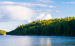 Lake summer view with reflection of clouds on water, Finland Stock Photos