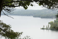 Lake Sunapee from Clark Landing in New London, New Hampshire. Tranquil view of Lake Sunapee framed by branches, from Clark Landing in New London, New Hampshire stock image