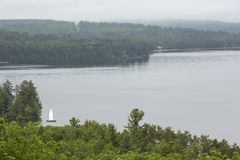 Lake Sunapee from Clark Landing in New London, New Hampshire. Tranquil view of Lake Sunapee with a lighthouse, from Clark Landing in New London, New Hampshire royalty free stock image