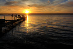 Lake Sunrise. A beautiful autumn sunrise on the pebbled shores of Lake Cayuga in the Finger lakes region of New York state. A pier leads out to a deck with Stock Photography