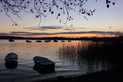 Lake at sunrise with boats. View of Lake Maggiore, Piemonte, Italy, at sun rise with two boats and reeds Royalty Free Stock Photography