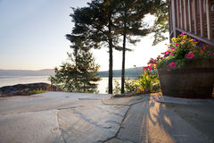 Lake sunrise from patio. Early morning sun spills onto a lakeside patio and flower barrel Royalty Free Stock Photos