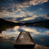 Lake at sunset. Wide-angle shot of a jetty and lake with a dramatic sky reflected in the water Stock Photography