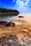 Lake sunset. Beautiful view on a rocky shore with clear water and golden reflections at sunset. Georgian Bay, Canada Royalty Free Stock Photo