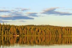 Lake at sunset among dense forest. Travel, Scandinavia, fishing Stock Photography
