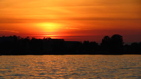 Lake sunset. Fire orange clouds over shoreline as the sun fades between clouds Royalty Free Stock Images