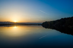 Lake at sunset with a jet passing Royalty Free Stock Image