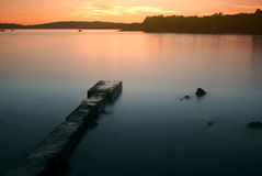 Lake sunset. Pier on lake sunset landscape Royalty Free Stock Photography