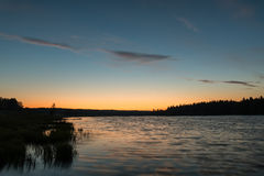 Lake sunset sky clouds. Scenic orange and blue sunset on the lake with clouds reflecting in water Stock Photography