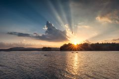 Lake sunset with sun beams royalty free stock photography