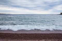 Lake Superior Beach and Waves. Waves over the rocks on the North Shore of Lake Superior in Minnesota royalty free stock photo
