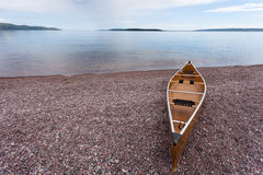 Lake Superior Ontario Canada canoe water landscape. Canoe beached on gravel shore of calm Lake Superior water wilderness of Ontario, ON, Canada, ready for an Royalty Free Stock Image