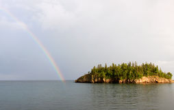 Lake Superior Rainbow. Photograph of a brilliant rainbow touching the waters of Lake Superior while the afternoon sun lightens up the trees of a nearby island stock images