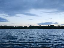 Lake surface at evening in Latvia, East Europe. Landscape with water and forest. stock photography
