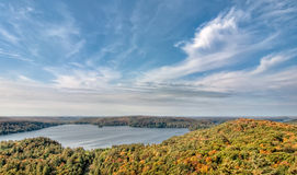 Lake Surrounded by Fall Trees and Whispy Clouds Stock Photos