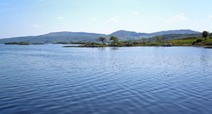 Lake surrounded by hills. A calm lake surrounded by green hills royalty free stock images
