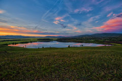 Lake surrounded hills and meadows, red-yellow-blue sky Stock Images