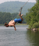 Lake Swing. Man diving into lake from a classic rope swing Stock Photo