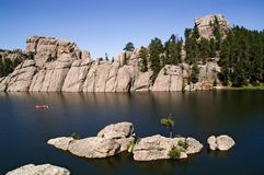 Lake Sylvan, South Dakota. Peaceful clear water, blue sky and lonely boat in the lake Stock Photos