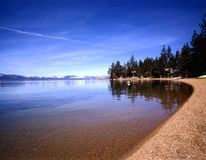 LAKE TAHOE. Shores of lake with snow covered mountains in background Stock Photography
