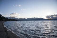 Lake Tahoe Beach Sunset. Lake shore with mountains in background at sunset stock photo