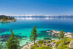 Lake Tahoe. Calm turquoise waters with view on Sierra Nevada snowy peaks stock photography
